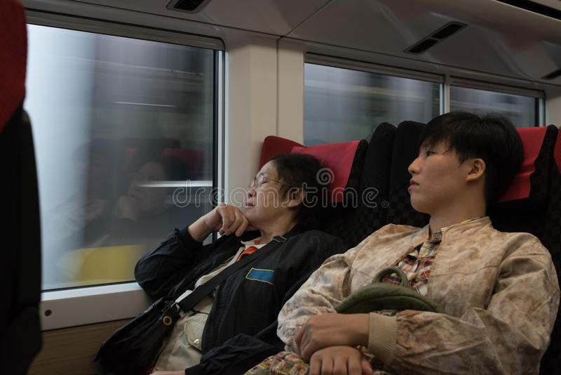 Due della donna asiatica delle signore si siedono in treno, un sonno, un throug di sguardo immagine stock libera da diritti