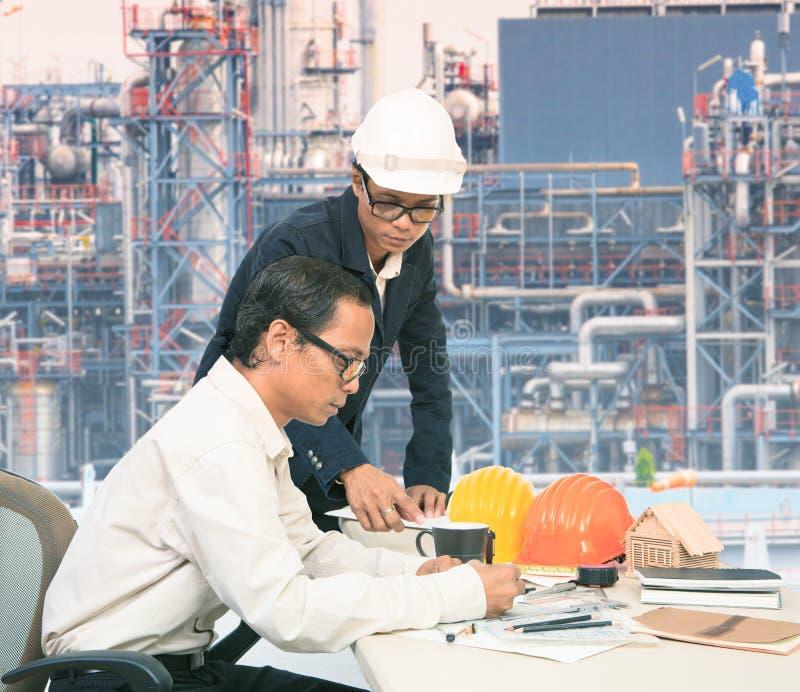 Due dello stesso ingegnere che lavora alla tavola contro l'esterno della raffineria di petrolio p fotografia stock