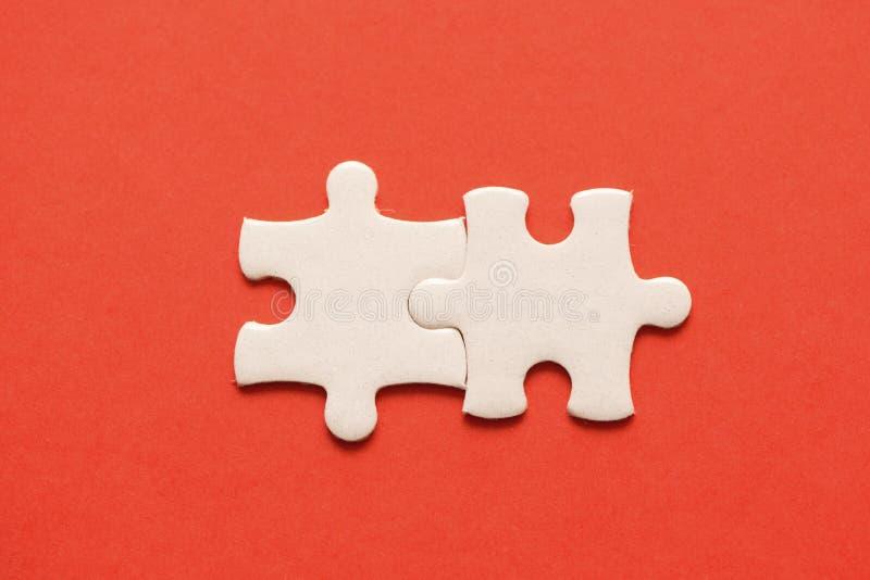 Due dettagli bianchi del puzzle su fondo rosso immagine stock