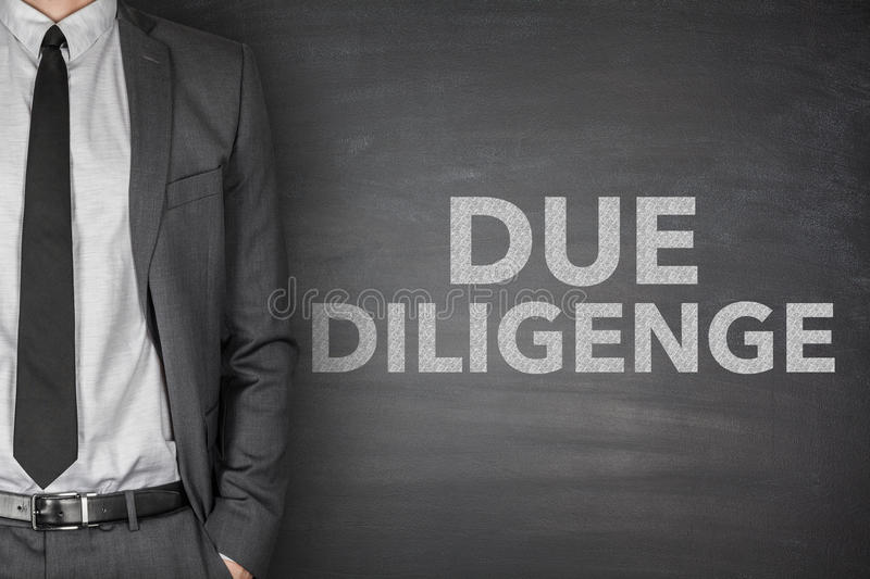 Due diligence on blackboard. Due diligence on black blackboard with businessman stock photo