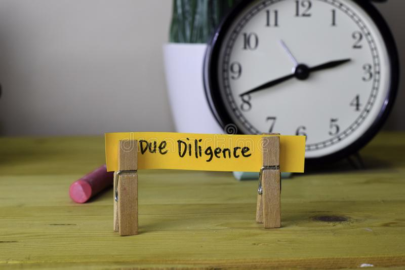 Due Diligence. Handwriting on sticky notes in clothes pegs on wooden office desk royalty free stock photography