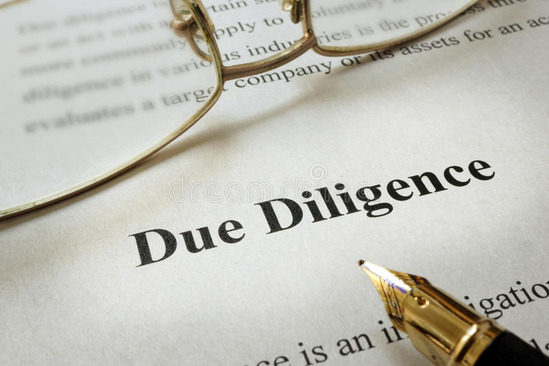 Due Diligence. Page of paper with words Due Diligence and glasses stock images