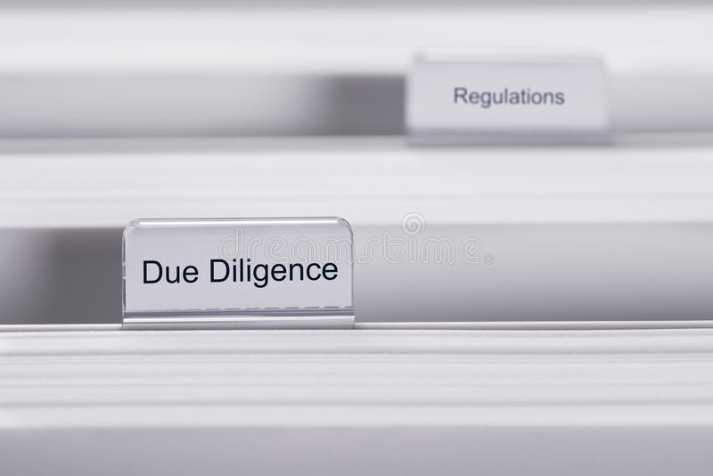 Due diligence and regulations folders. Closeup of folders marked with Due Diligence and Regulations stock photography