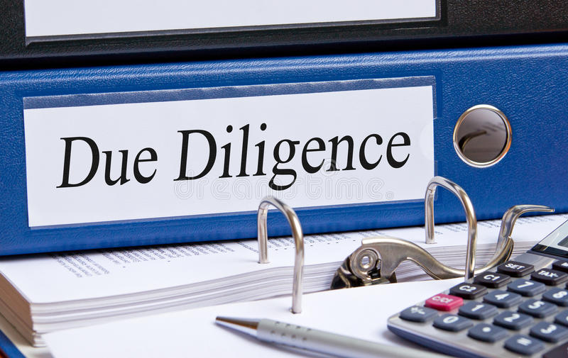Due Diligence. Text 'Due Diligence' on a white label fixed to a blue folder place on a desk with another binder and calculator, concept of checking business royalty free stock images