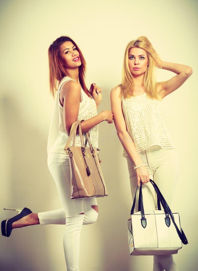 Due donne in abiti bianchi con borse immagini stock