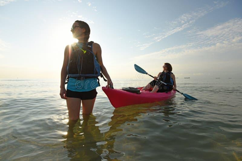 Due donne adatte dei giovani in kajak immagini stock