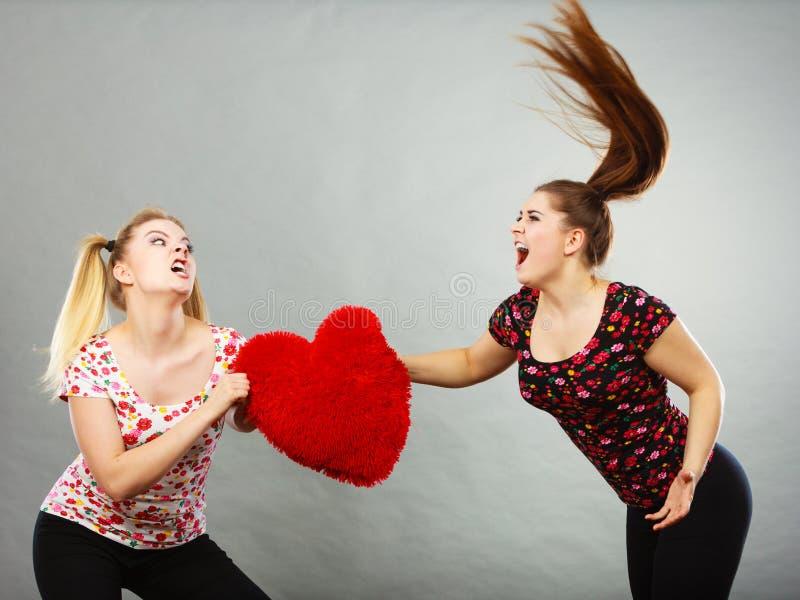 Due donne aggressive che hanno discutono il cuore della tenuta di lotta fotografie stock libere da diritti