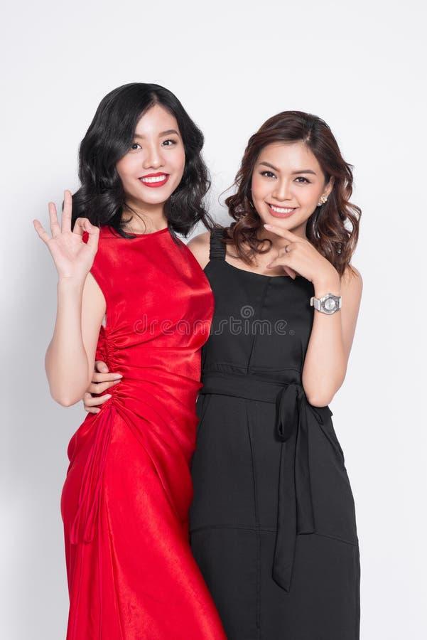 Due donne alla moda in vestiti piacevoli che stanno insieme e in havi fotografia stock libera da diritti