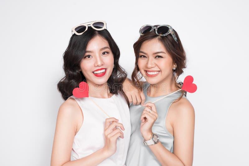 Due donne alla moda in vestiti piacevoli che stanno insieme e nella tenuta immagine stock libera da diritti