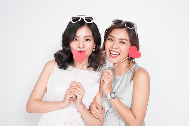 Due donne alla moda in vestiti piacevoli che stanno insieme e nella tenuta fotografia stock