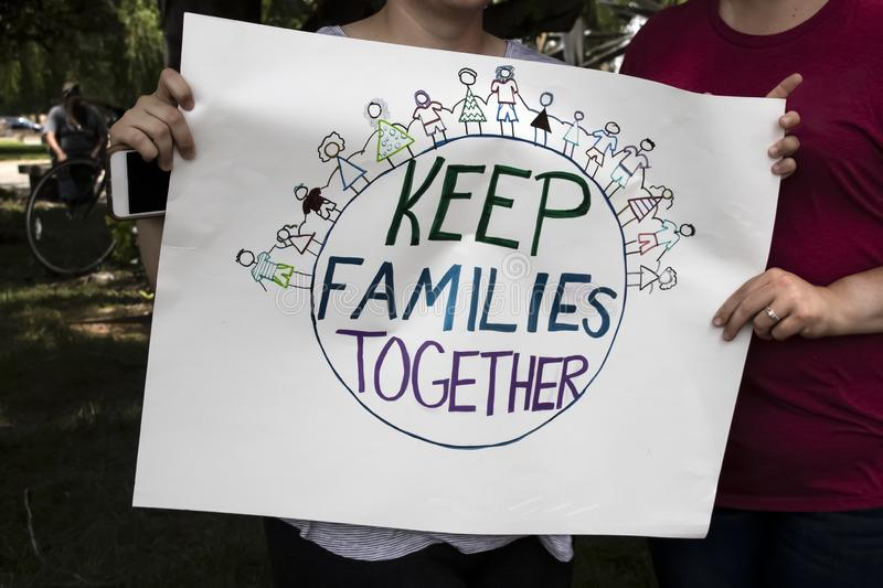 Due donne alla protesta che iscenano il segno casalingo che dice tengono insieme le famiglie insieme al mondo e le famiglie che s immagine stock