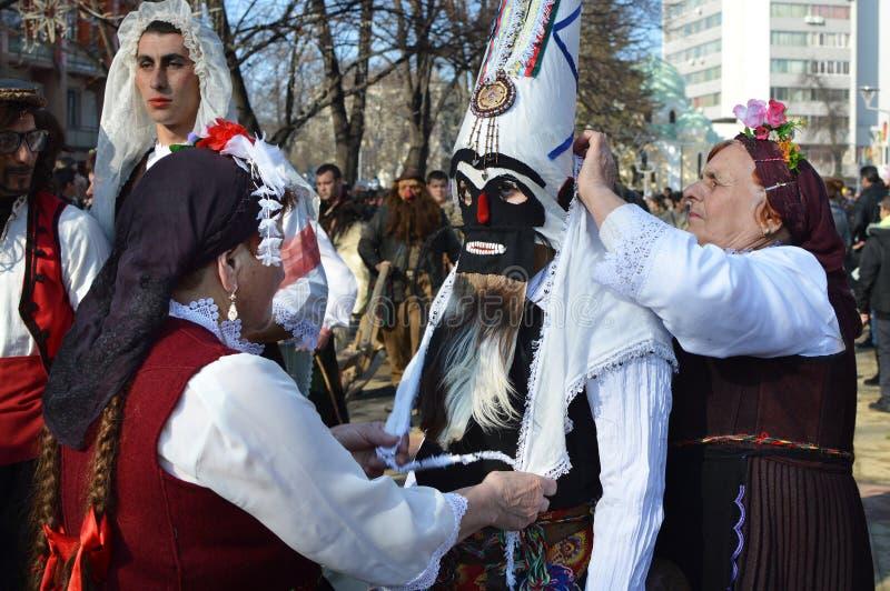 Due donne anziane con i costumi pieghi tradizionali aiutano una ragazza con la sua maschera del kuker fotografia stock