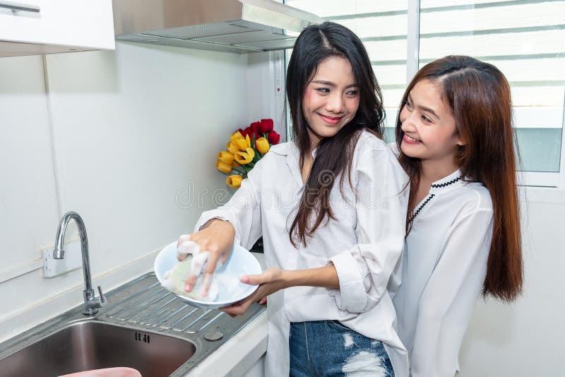 Due donne asiatiche che lavano insieme i piatti nella cucina La gente e concetto di stili di vita Orgoglio di LGBT e tema delle l immagine stock