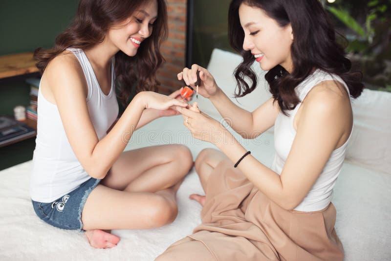 https://thumbs.dreamstime.com/b/due-donne-asiatiche-nella-camera-da-letto-sul-dipingono-i-loro-chiodi-e-99609197.jpg