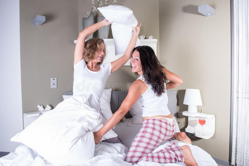 Due donne attraenti che hanno una lotta di cuscino a letto fotografia stock immagine di vetri - Foto di donne a letto ...