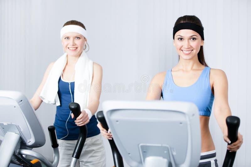 Due donne che addestrano sull'apparecchiatura di addestramento in ginnastica fotografia stock libera da diritti