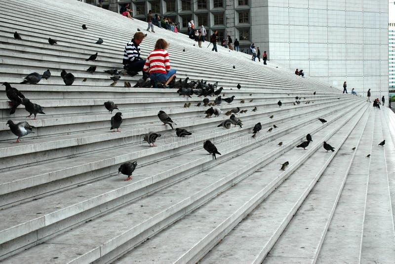 Due donne che alimentano i piccioni sulle scale fotografia stock