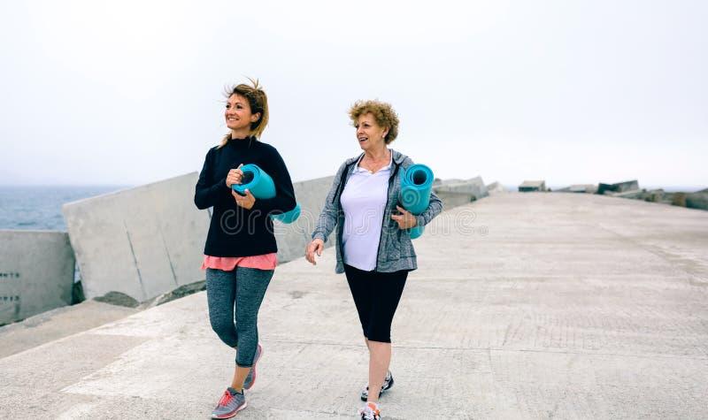 Due donne che camminano dal pilastro del mare immagine stock