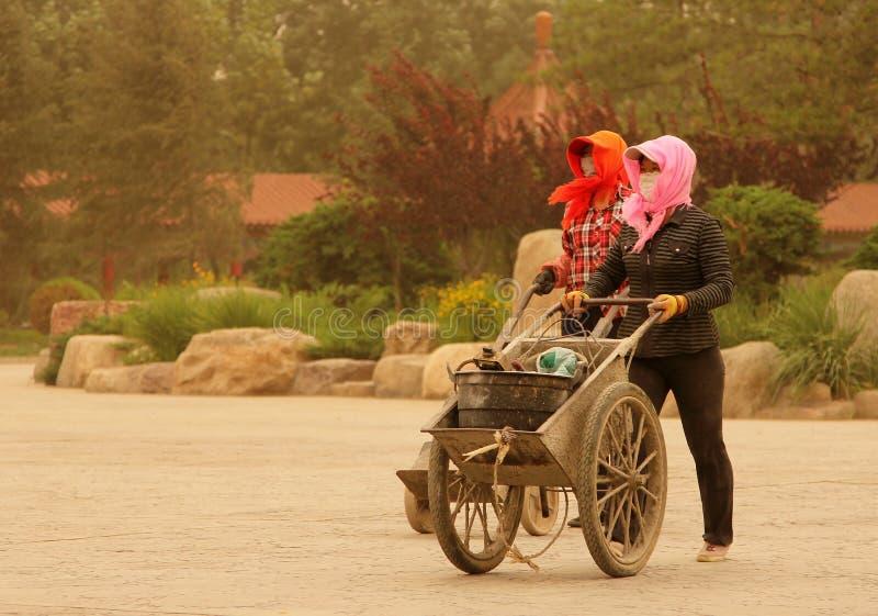 Due donne che camminano sulla via durante la tempesta di sabbia, porcellana fotografia stock