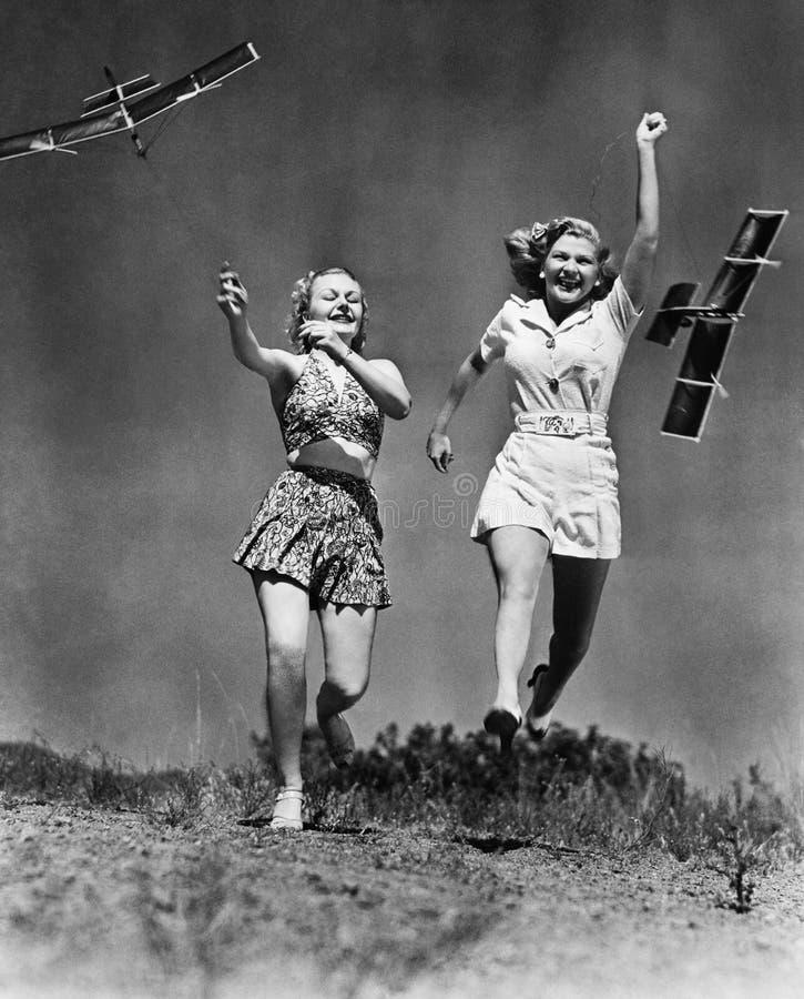 Due donne che corrono e che giocano con gli aeroplani di modello (tutte le persone rappresentate non sono vivente più lungo e nes fotografia stock