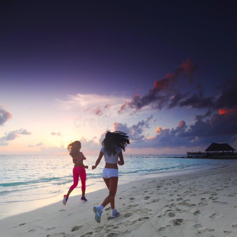 due donne che corrono sulla spiaggia fotografia stock