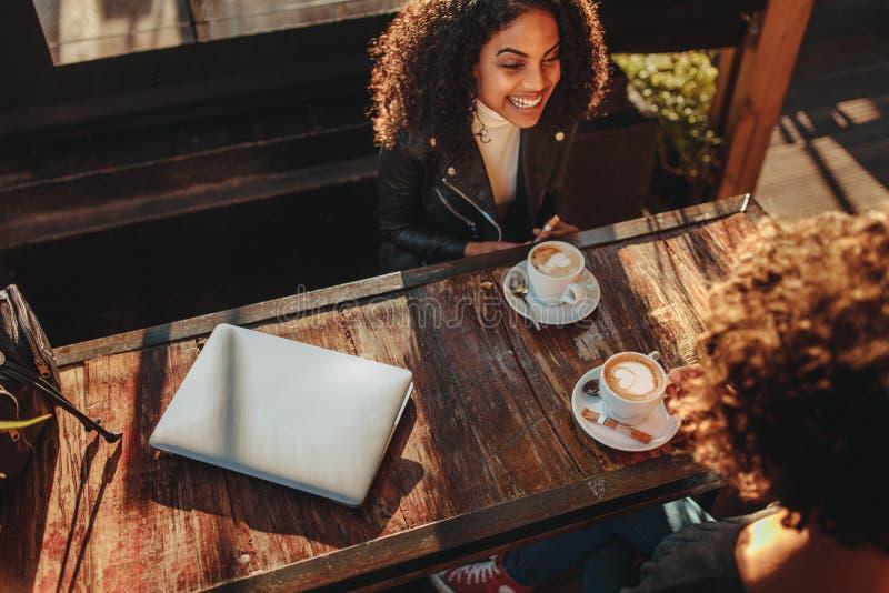 Due donne che discutono a fondo caffè ad una caffetteria immagini stock libere da diritti
