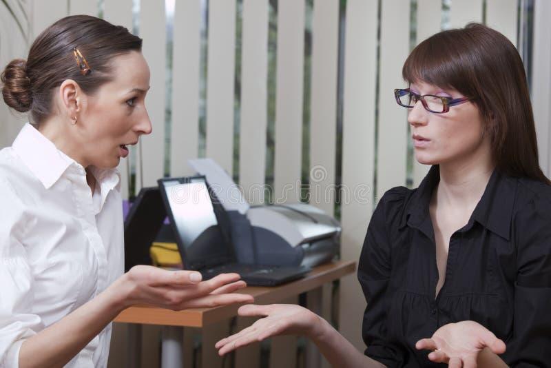 Due donne che discutono nell'ufficio fotografia stock