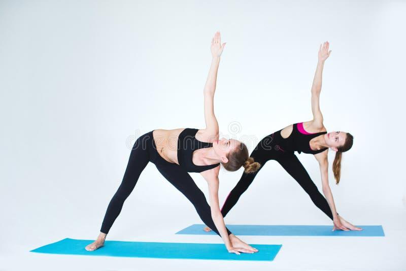 Due donne che fanno allungando gli esercizi nello studio fotografie stock