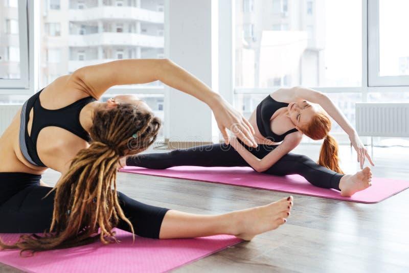 Due donne che fanno gli esercizi e che allungano nello studio di yoga fotografia stock libera da diritti