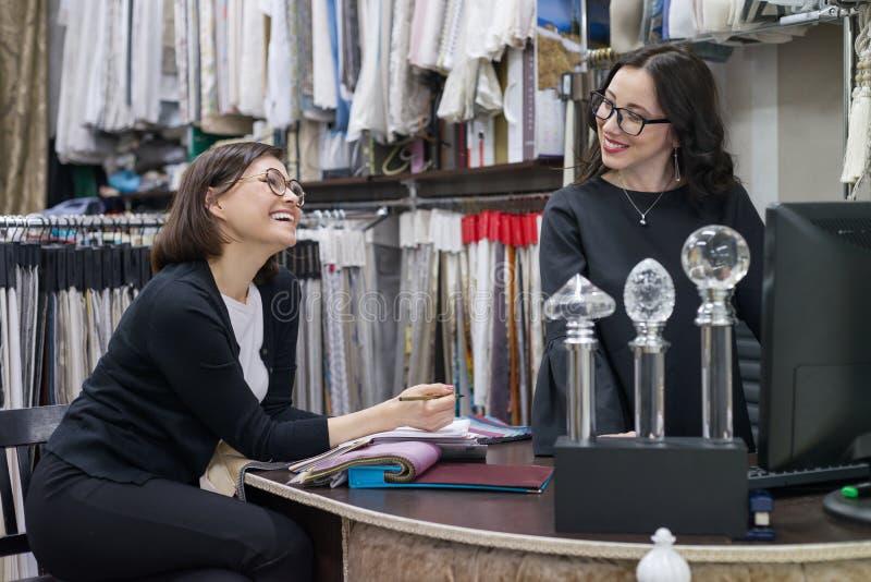 Due donne che lavorano con i tessuti per le tende, tappezzeria, femmine sorridenti scelgono i tessuti facendo uso del computer Pr fotografia stock libera da diritti