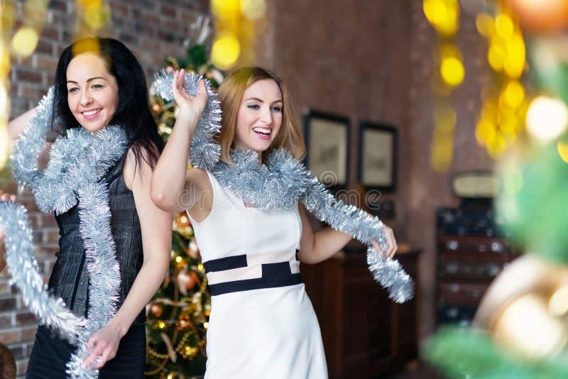 Due donne che portano i vestiti che ballano mentre divertendosi sul partito del nuovo anno immagini stock libere da diritti