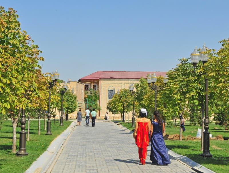 Due donne che portano i vestiti nazionali camminano dalla via fotografia stock libera da diritti
