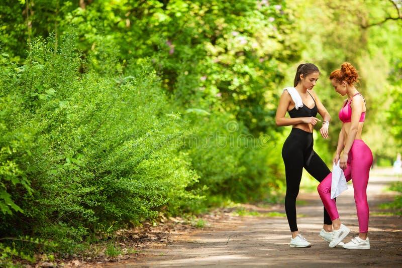 Due donne che si esercitano nel parco Giovane bella donna che fa insieme gli esercizi all'aperto fotografia stock libera da diritti