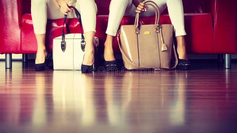 Due donne che si siedono sul sof? che presenta le borse fotografia stock libera da diritti