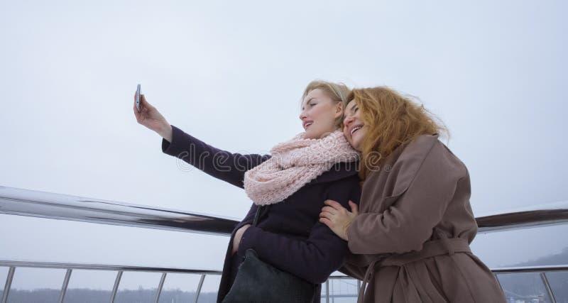 Due donne che si sparano, giorno della nuvola, all'aperto fotografie stock