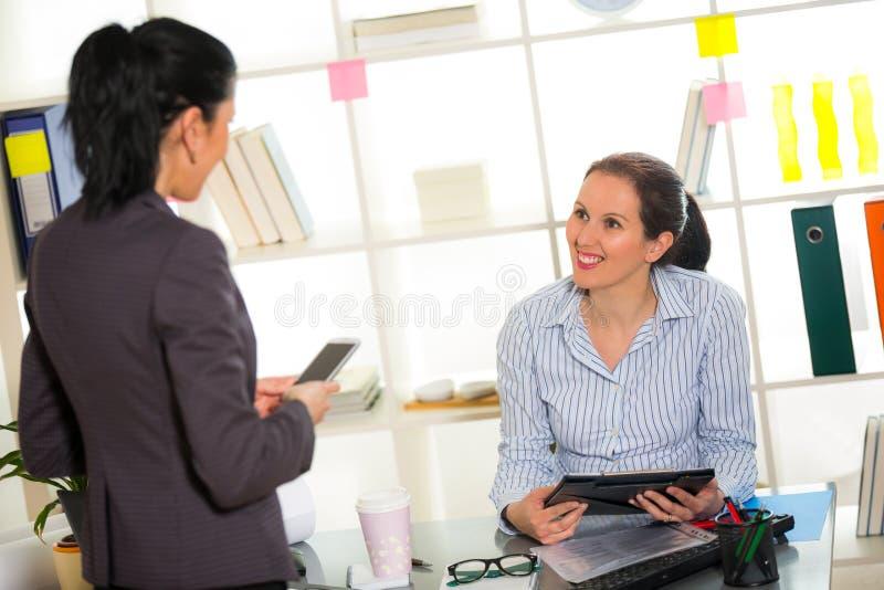 Due donne chiacchierano l'un l'altro nell'ufficio fotografia stock