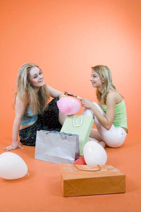 Due donne con i sacchetti e gli aerostati di acquisto immagine stock libera da diritti