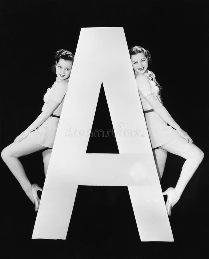 Due donne con la lettera enorme A (tutte le persone rappresentate non sono vivente più lungo e nessuna proprietà esiste Garanzie  immagine stock