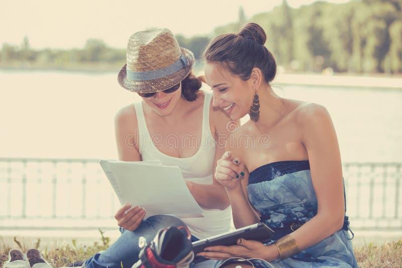 Due donne degli amici all'aperto che studiano e che sembrano felici fotografia stock