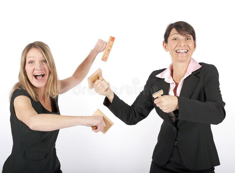 Due donne di affari che combattono con i timbri di gomma fotografia stock libera da diritti