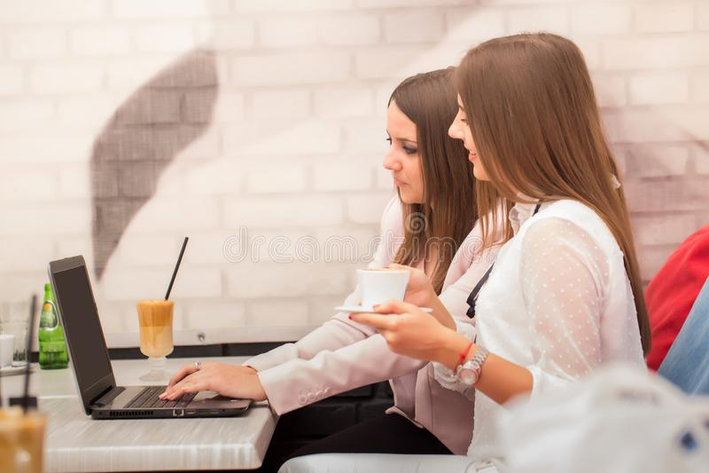 Due donne di affari che lavorano al computer portatile in caffetteria fotografia stock libera da diritti