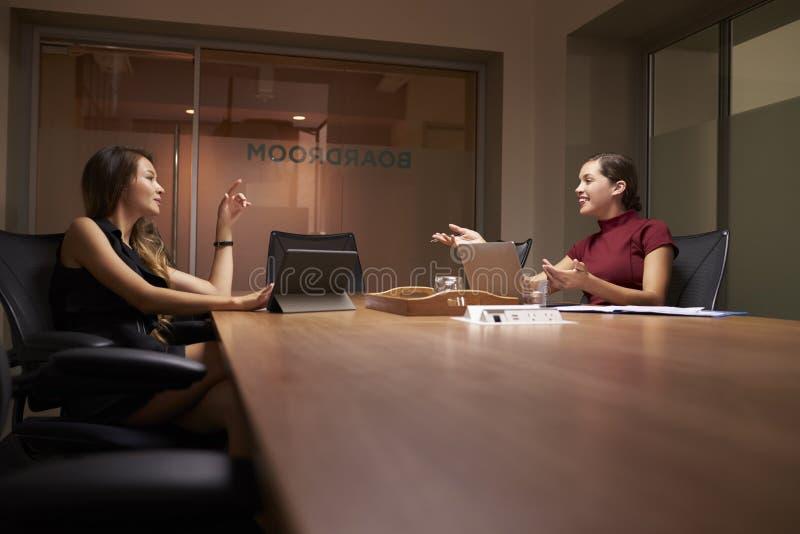 Due donne di affari che lavorano tardi in una conversazione dell'ufficio immagini stock libere da diritti