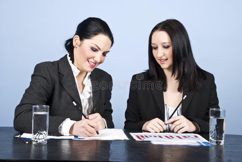 Due donne di affari che scrivono nell'ufficio immagini stock