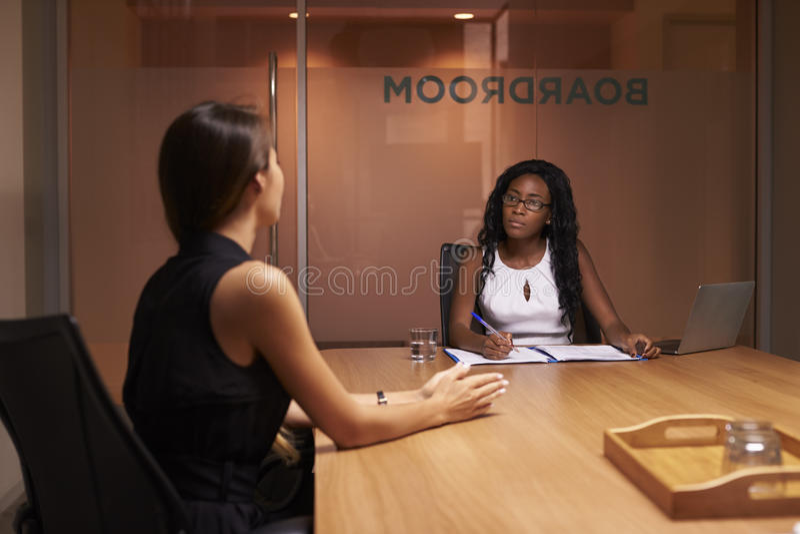 Due donne di affari corporative ad una riunione di sera nell'ufficio immagini stock libere da diritti