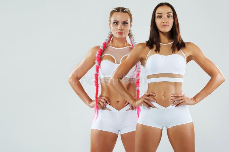 Due donne di atletica di forma fisica in abiti sportivi isolati su fondo bianco Concetto di modo e di sport con lo spazio della c fotografia stock