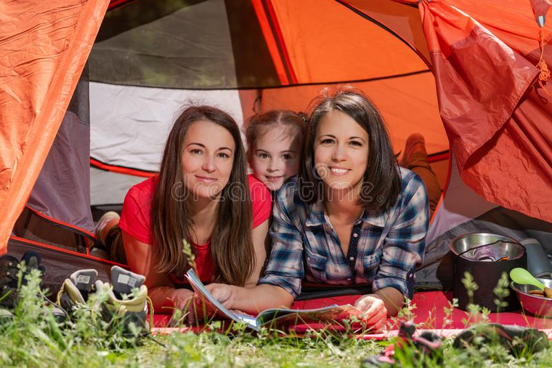 Due donne e bambino alla tenda di campeggio fotografia stock libera da diritti