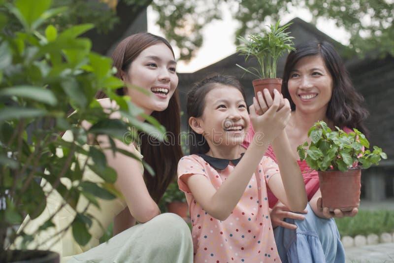 Due donne e ragazza che sorridono e che fanno il giardinaggio, tenenti le piante fotografie stock libere da diritti