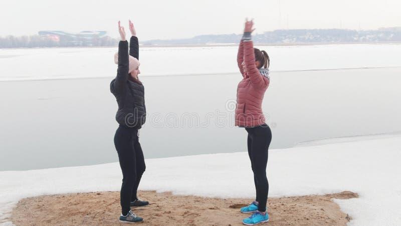 Due donne esili che stanno sulla spiaggia nevosa e che si scaldano per il funzionamento Mettendo le loro mani fino al cielo fotografia stock