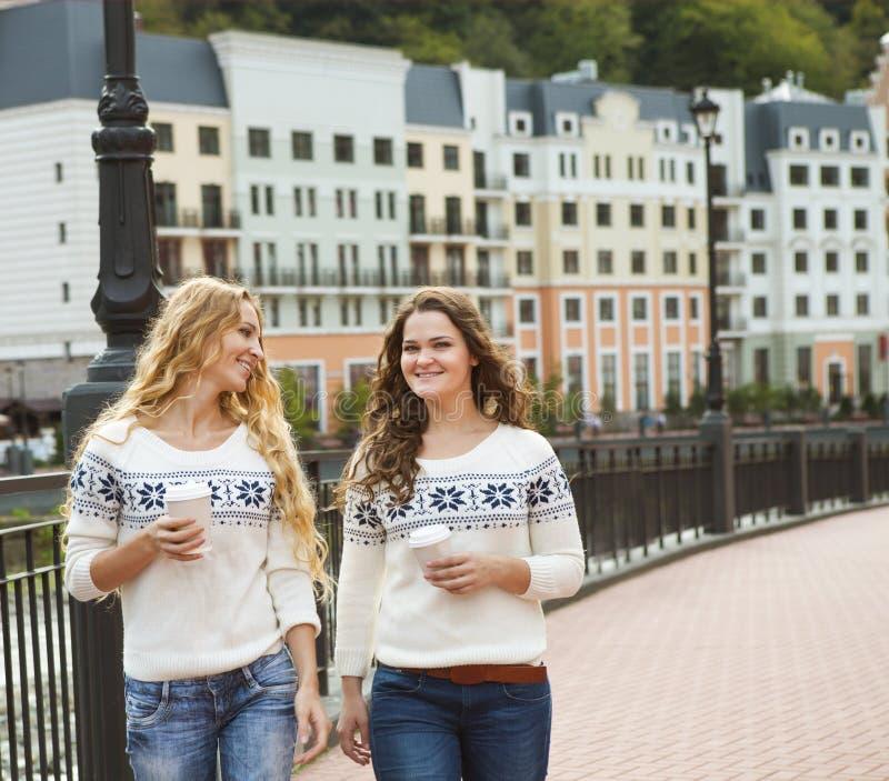 Due donne felici casuali che hanno una conversazione mentre camminando in Th fotografia stock libera da diritti