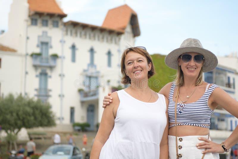 Due donne felici che posano in un villaggio mediterraneo fotografia stock